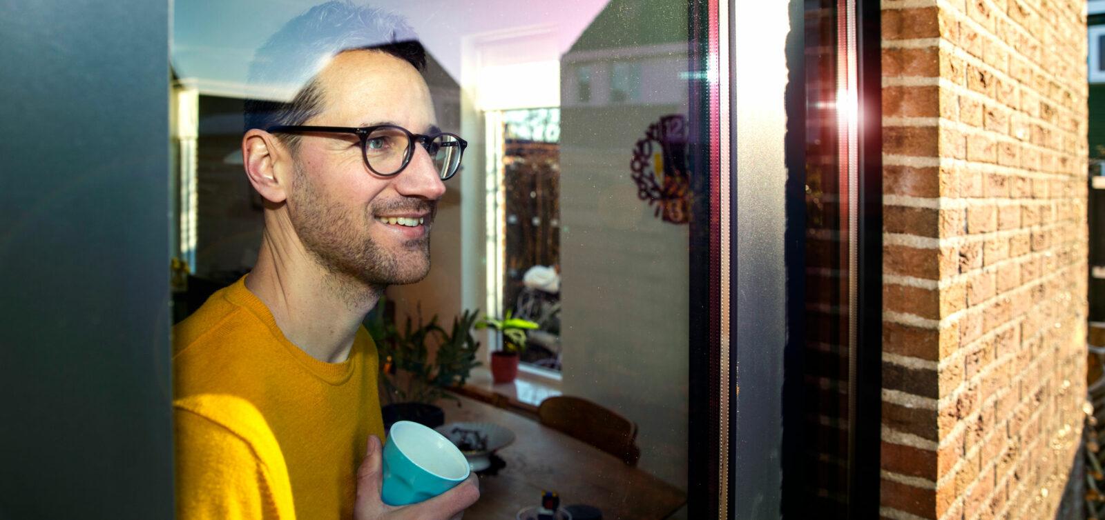 Sander voor het raam in zijn aardgasvrije woning